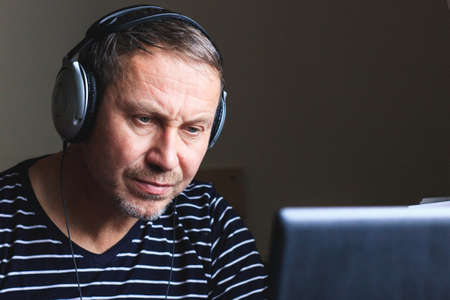 Middle-aged man in headphones at the computer undergoes a training course Фото со стока