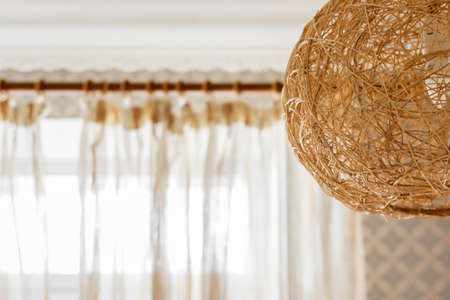beautiful round wicker rattan lampshade combined with delicate translucent curtains. Interior design