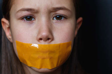 Unhappy girl with sticky tape over her mouth. Violation of human rights. Stock Photo