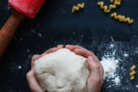 Dough in the child hands. Rolling pin, flour on the table. Top view .