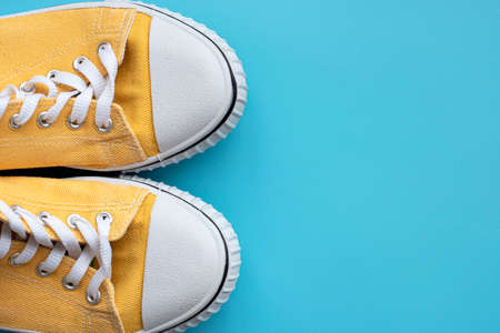 Yellow summer youth sneakers on a blue background Foto de archivo