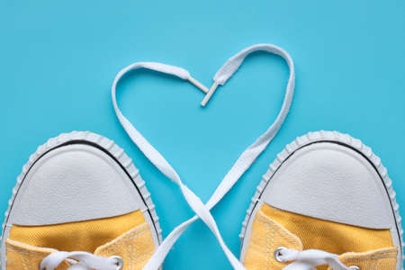 Yellow summer youth sneakers on a blue background with copy space