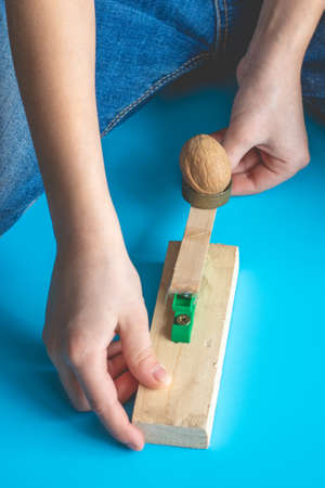 A child shoots a walnut at a target from a handmade catapult Imagens