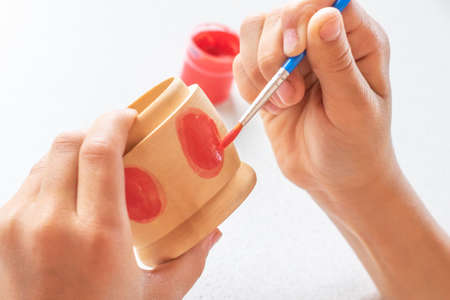 A child paints a wooden blank of a nesting doll. Children's crafts