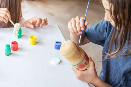 A child paints a wooden blank of a nesting doll. Children's crafts Banco de Imagens
