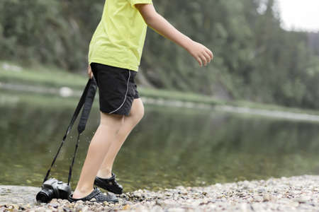 A boy stands in the river on outdooor and destroys a mirrorless photo camera. The concept of obsolescence of technology. Photographers day, humor. Summer day, forest. Stockfoto