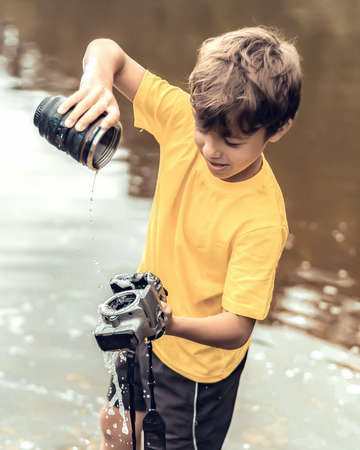 A schoolboy stands in the river on outdooor and destroys a mirrorless photo camera. The concept of obsolescence of technology. Photographers day, humor. Toned picture. Soft light photo.