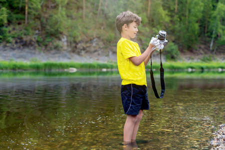 A schoolboy is standing in outdoor near the river, holding a photo camera in his hands and washing, cleaning it with soap and foam. The concept boy is a vandal. The risk of damage to equipment.