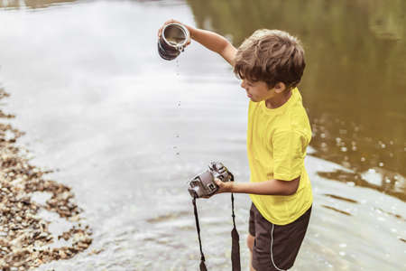 A child stands in the river on outdooor and destroys a mirrorless photo camera. The concept of obsolescence of technology. Photographers day, humor. Toned picture. Soft light. Imagens