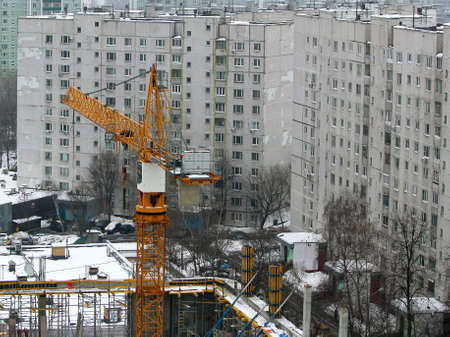 Orange construction crane close-up. Construction of new housing. Buying an apartment in a residential building.