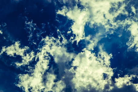 Fluffy white solar clouds in the twilight light float against the dark blue sky. Divine view. Concept and background dream, integrity, wholeness, unity, totality, Halloween.