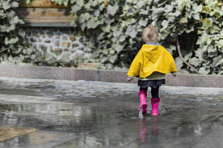 A nice little girl in a yellow raincoat and pink rubber boots jumps on puddles with splashes and rejoices. Park, nature, outdoors. Summer. Universal Children's Day.