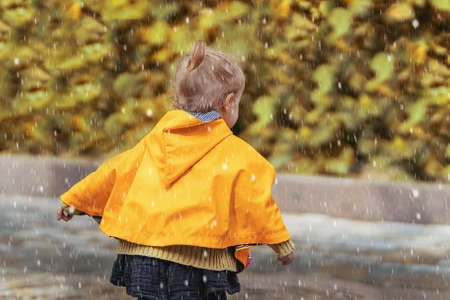 A happy small girl in a yellow raincoat walking in the rain on the street alone. Park, nature, outdoors. Childhood concept. Universal Children's Day.