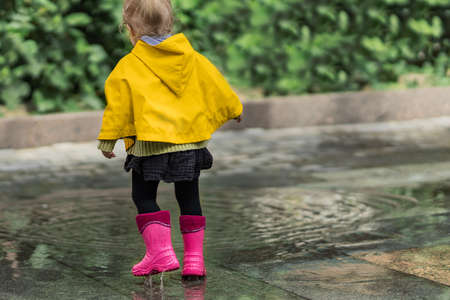 A nice little girl in a yellow raincoat and pink rubber boots jumps on puddles with splashes and rejoices. Park, nature, outdoors. Summer season. Universal Children's Day. 免版税图像