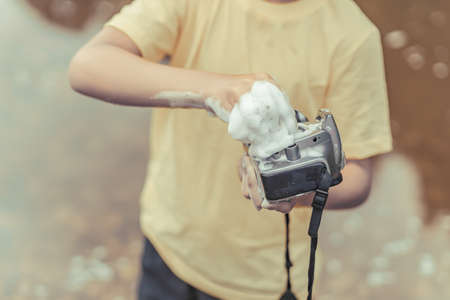 A boy in a yellow t-shirt and shorts is standing near the water on outdoor and cleaning a camera with soap and foam. The concept photographers day. Toned brown photo. Close up.