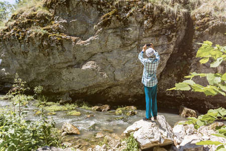 A teenager in turquoise trousers and a plaid shirt stands on a stone near the river and take a photo the rock with moss on a mobile phone in the bright sunlight. Daytime, mountain landscape.