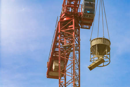 Red tower crane with cement mixer against blue sky with white clouds. Close up. Front shot. Glare of the sun on the cabin builder. backdrop