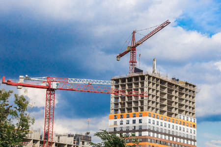 Several red cranes have been put to work on the construction of a modern multi-storey residential complex against a blue sky with white clouds. Concept work for people with the profession of builder.