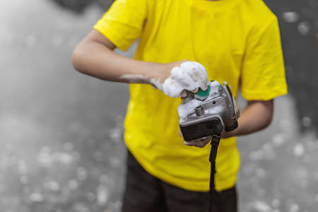 A schoolboy in a yellow t-shirt and shorts is standing near the water in nature and washing a camera with soap and foam. The concept joke and humor. Bright color photo. Close up. Фото со стока