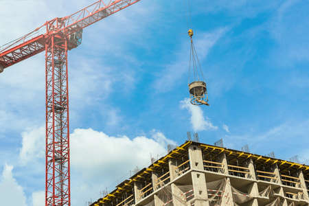 One high-rise crane with cement mortar against a house and blue sunny sky during the construction phase. Industry concept for low-income young families. Mortgage, business, real estate loan. Reklamní fotografie