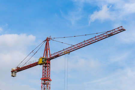 Red tower crane against light blue sky with white clouds. Close up. Copy space.