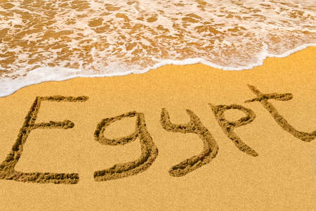 Egypt title on the sand beach of the Red sea. Hot season. Wave.