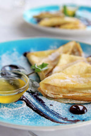 baked pancakes with mint honey powdered sugar and sauce on blue plate