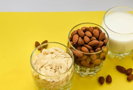 almond nuts in the glass and almond chips and almond milk in the glass on the white and yellow background, copy space, Making almond milk from dried almonds