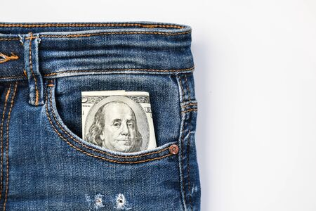 American dollar banknote in a pocket of blue jeans, franklin watching from pocket copy space
