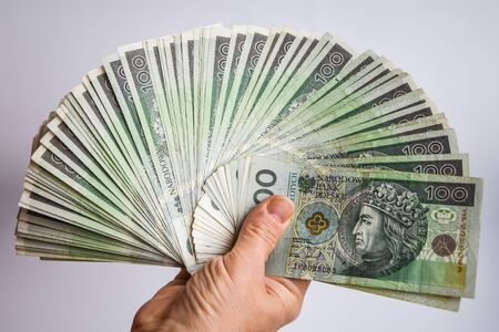 polish zloty currency, poland money, hand holding polish cash on the white background Polish Zloty Trading Business Theme