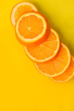 Fresh and Juicy Orange fruit slices on the yellow background, healthy food