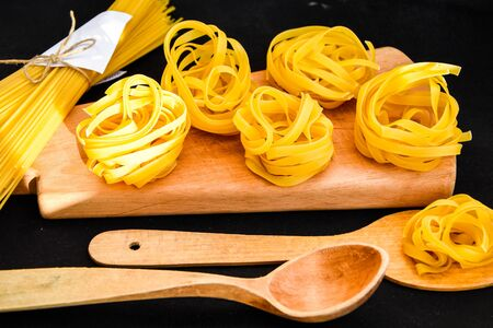 Raw dry spaghetti and tagliatelle round balls of pasta with wooden spoon on the wooden cutting board on the black background, Italian cuisine. Stock fotó