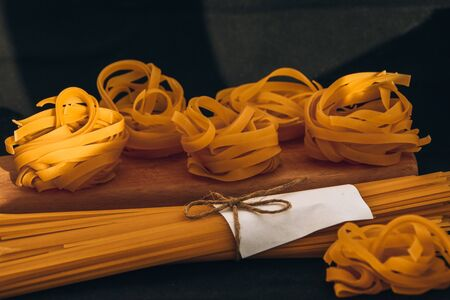 Raw dry spaghetti and tagliatelle round balls of pasta on the wooden cutting board on the black background, Italian cuisine.