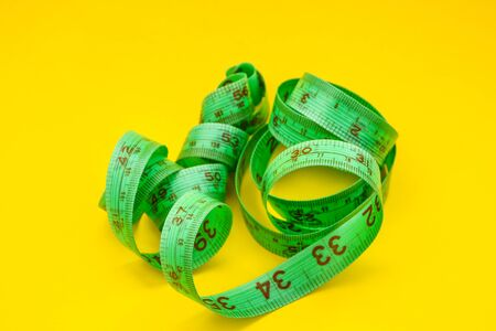 Close Up Tailor Measuring Tape on the yellow Background, Perspective view of spiral measuring tape, Close up of slimming concept
