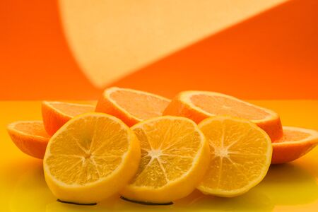 Fresh and Juicy Orange and Lemon fruit slices on the yellow background, healthy food