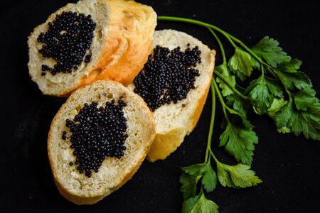 three tasty sandwiches with black caviar with green parsley on the dark background, baguette slices and caviar Luxurious culinary delicacy