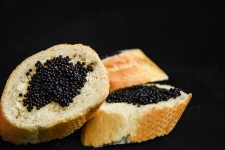 three tasty sandwiches with black caviar on the dark background, baguette slices and caviar Luxurious culinary delicacy Zdjęcie Seryjne
