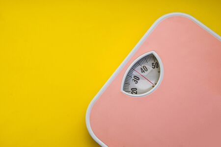 Modern pink weight scale on the yellow background, top view, copy space, Fitness concept
