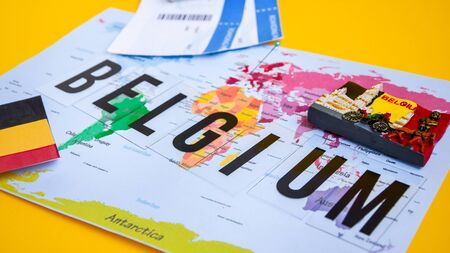 Belgium travel concept, passport with boarding pass, flag and magnet over world map with pin, Manneken Pis