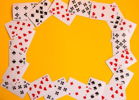 Frame with copy space of Playing cards on a yellow background close up, table games poker Imagens