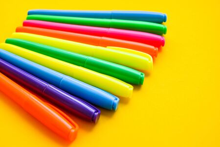 Felt-tip pens on a yellow background with copy space, set of new bright plastic opened colored felt pens near the caps . concept of office supplies