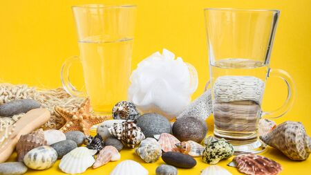 Glass of water against yellow background with seashell starfish and stones, hot summer vacation or holiday concept