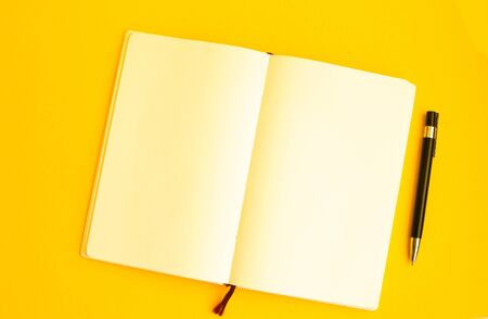 Top view of Blank notebook with pen on yellow background, Freelance working environment view , copy space, headphones Archivio Fotografico