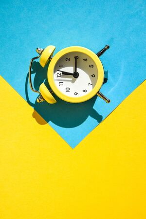 Yellow vintage alarm clock on a blue and yellow background with selective focus, copy space for text, The concept of time, delay, morning rise, the appointed meeting, Ringing twin bell vintage classic alarm clock, Rest hours time of life good morning night wake up awake concept.