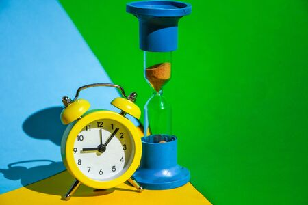 classic desktop clock, Hourglass colored background on yellow, green and blue, copy space, The concept of time, delay, morning rise, the appointed meeting, Ringing twin bell vintage classic alarm clock and sand clock 写真素材