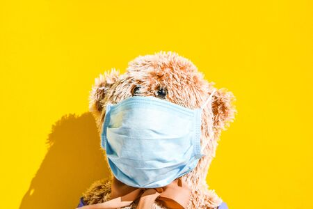 Coronavirus and Air pollution pm2.5 concept. Teddy bear in protection face mask isolated on yellow background with copy space, The concept of preserving health.Coronavirus protection. Medical care