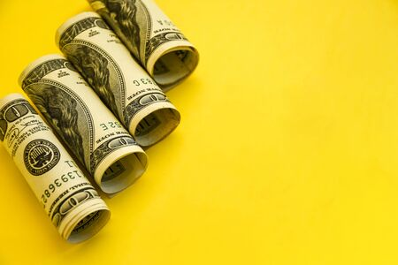 American dollars in rolls. Saving money concept on yellow background with copy space for text, Background from the dollar. American money. The American account, Savings and Wealth