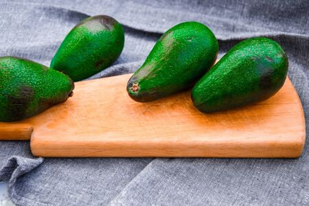 whole green avocado on the wooden tray and grey kitchen towel, vegetarian vegan food, healthy eating, dieting concept