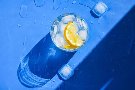 A glass of refreshing water with ice and lemon on a blue background. Heat concept, fresh. Natural light. Flat lay, top view, copy space, Soda water in glass glasses