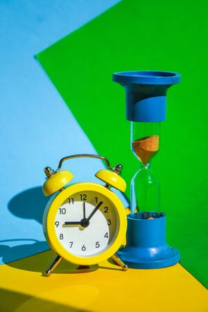 classic desktop clock, Hourglass colored background on yellow, green and blue, copy space, The concept of time, delay, morning rise, the appointed meeting, Ringing twin bell vintage classic alarm clock and sand clock 免版税图像